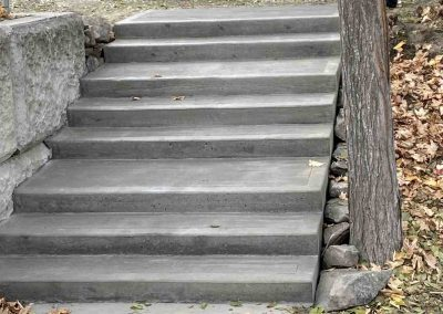 Completed concrete stairs leading down from street to front yard.