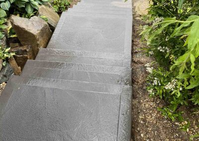 Concrete stairs leading down with textured finish.